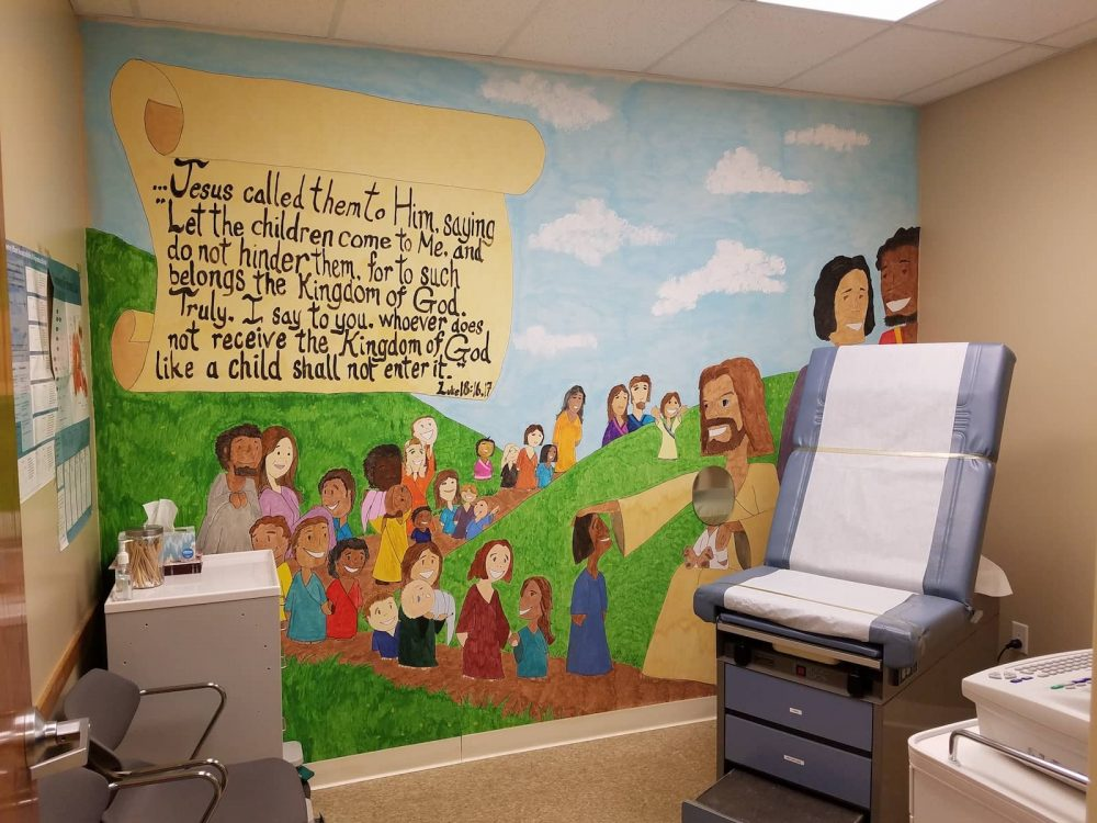 Oasis of Hope patient room with Christian mural