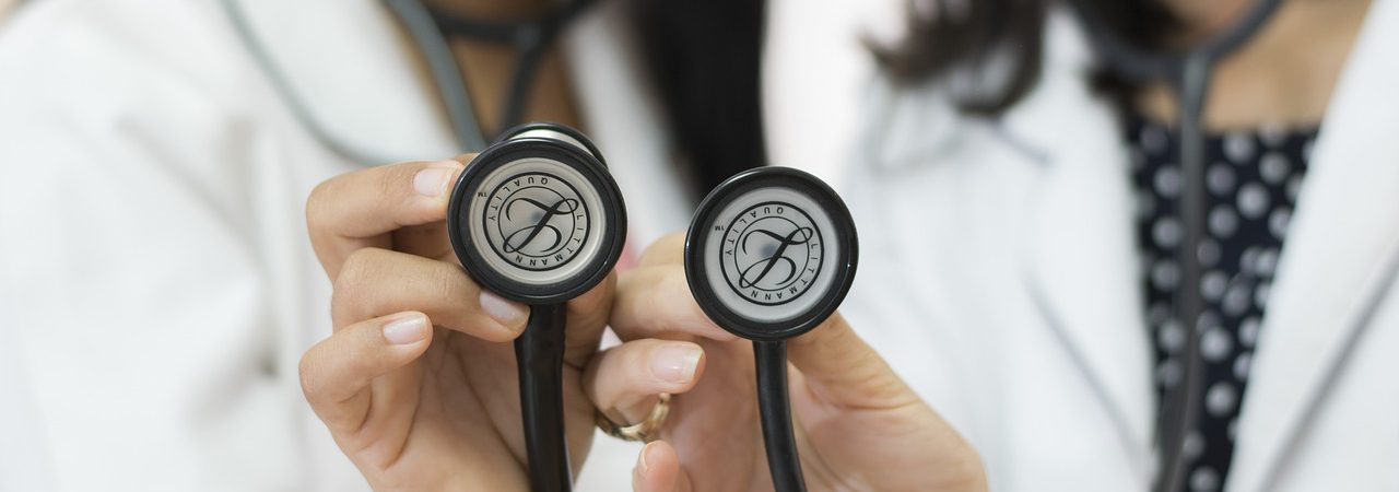 Two doctors holding a stethoscope up to the camera